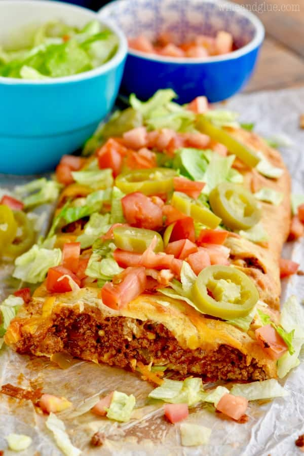 a taco braid that has been cut into and you can see the meat filling, topped with fresh tomatoes, lettuce, and jalapeños.
