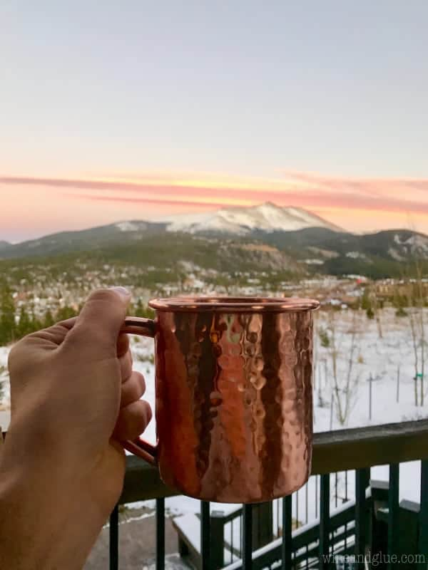 A woman holding a copper mug, and in the background are the beautiful Colorado Mountains.