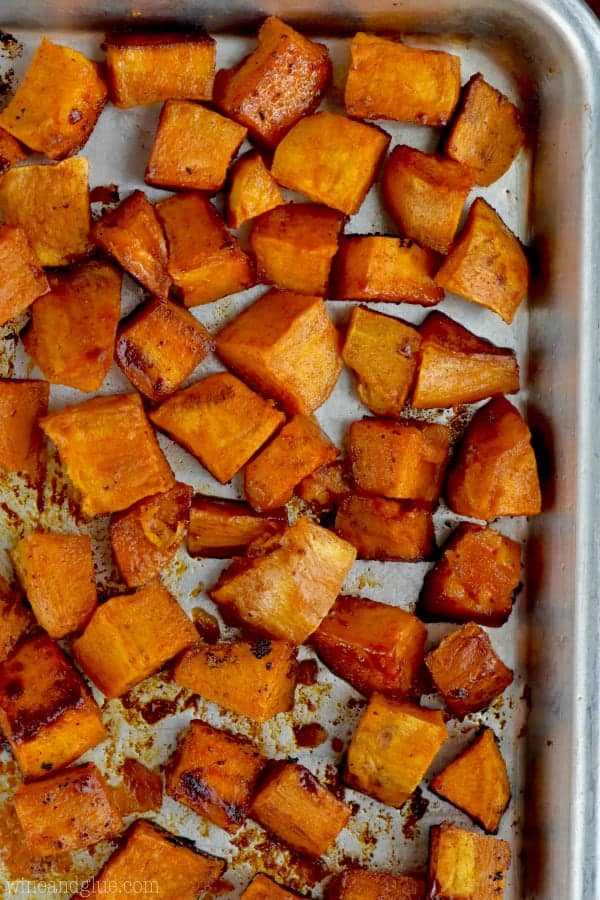 In a baking pan, the Sweet Potatoes are cut into cubes with some caramelization around the ages.