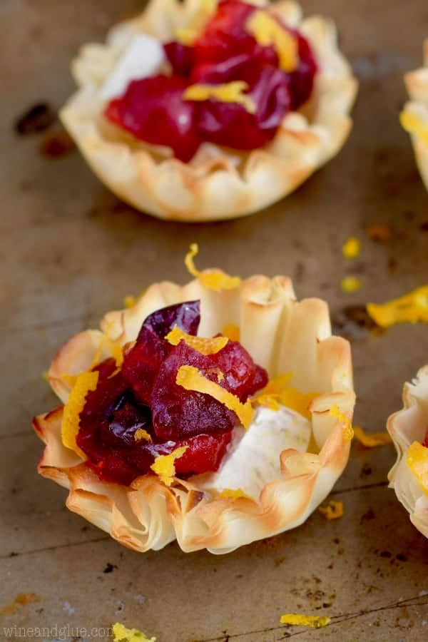 In a mini phyllo dough bowl, a small brie cheese topped with cranberry sauce and orange zest.