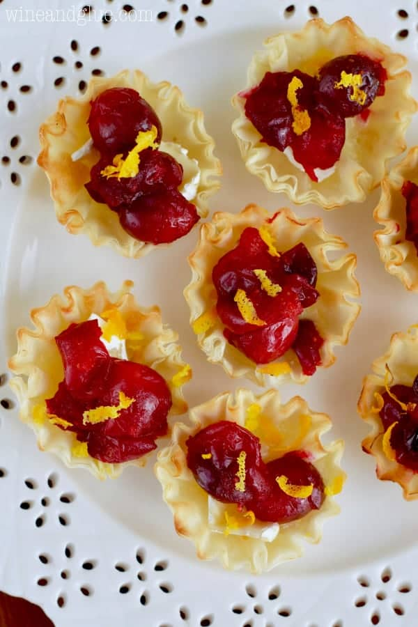 On a white plate, the Cranberry Brie Bites are topped with orange zest.
