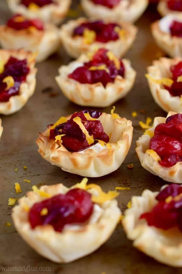 Lined up on a backing sheet, the Cranberry Brie Bites are topped with some Orange Zest.