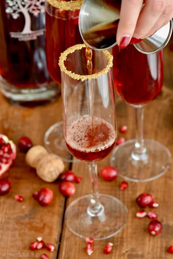 In a champagne fluke rimmed with golden sprinkles, the pomegranate liqueur is being poured.
