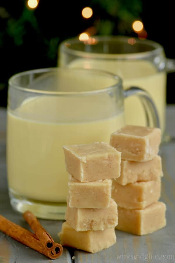 Two stacks of Eggnog Fudge are in front of two cups of Eggnog.