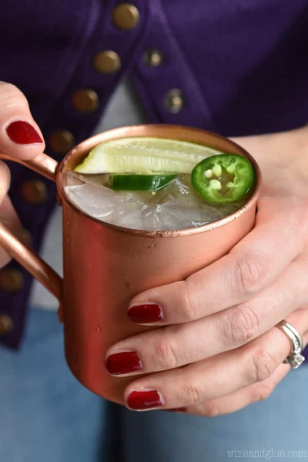 A woman holding a copper mug which has the Jalapeño Moscow mule with sliced Jalapeño and a lime