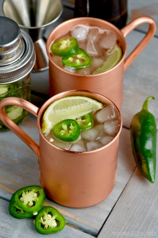 Two copper mugs filled with Jalapeño Moscow Mules with cut Jalapeño and limes.