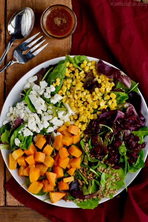 An overhead photo of the beautiful colorful Fall Salad which has feta cheese, butternut squash, cranberries, corn, greens, and sunflower seeds.