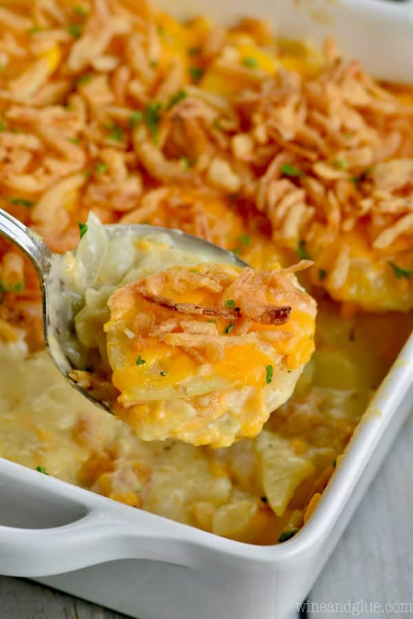 A scoopful of The Best Scalloped Potatoes coming out of the casserole dish.