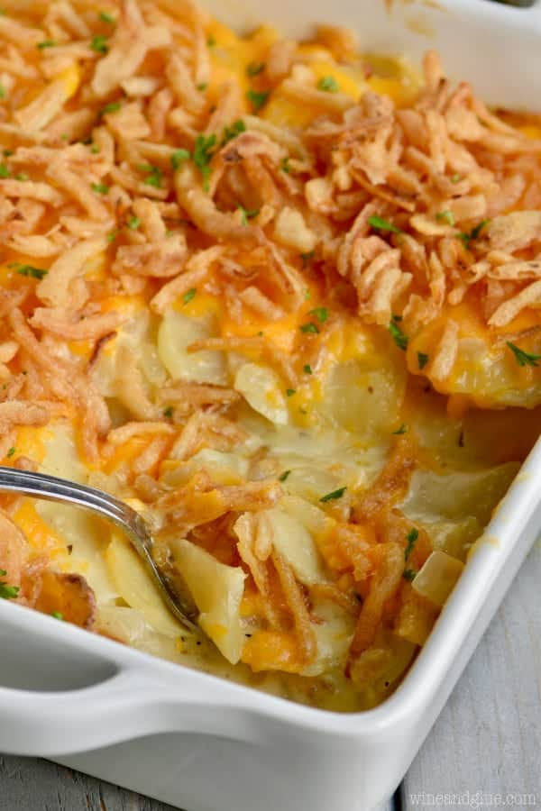 In a white casserole dish, the Best Scalloped Potatoes are topped with fried onions and parsley.