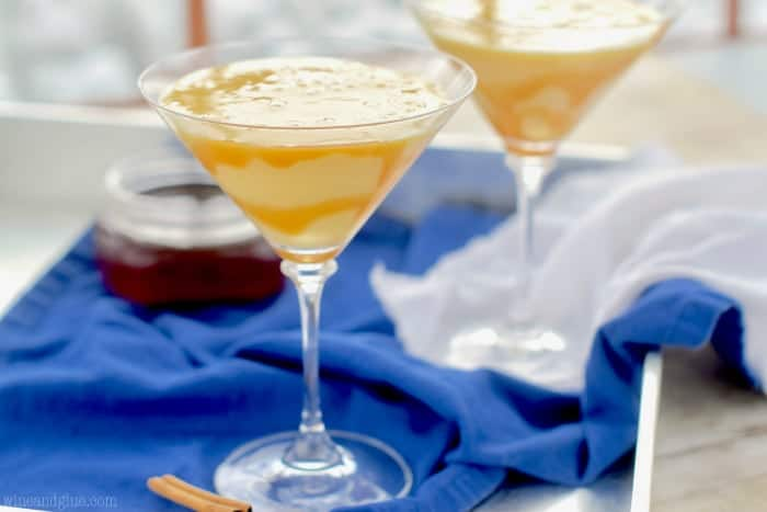 Two glass Eggnog Martinis with caramel dripping on the sides in the inside.