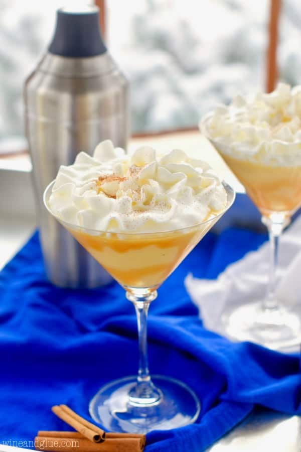 A glass of the Eggnog Martini with whip cream on top and caramel dripping on the sides.