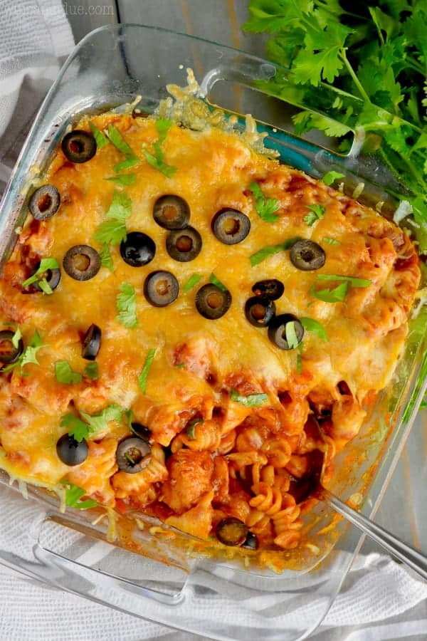 In a casserole dish, the Instant Pot Chicken Enchilada Casserole is topped with melted cheese, olives, and parsley.