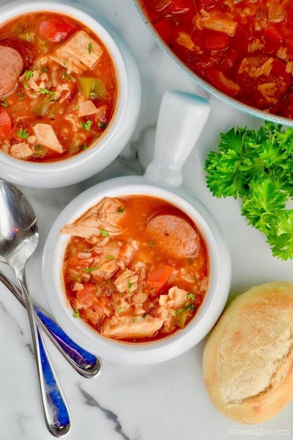An overhead photo of the Jambalaya Soup with a roll of bread on the side and topped with parsley.