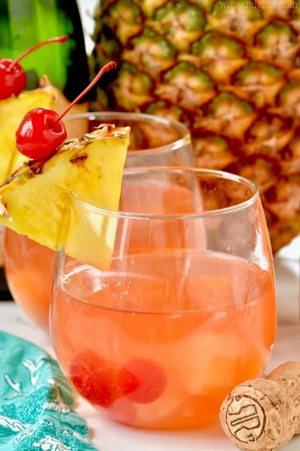 Two glasses of Pina Colada Rum Punch garnished with a slice of pineapple and a maraschino cherry.