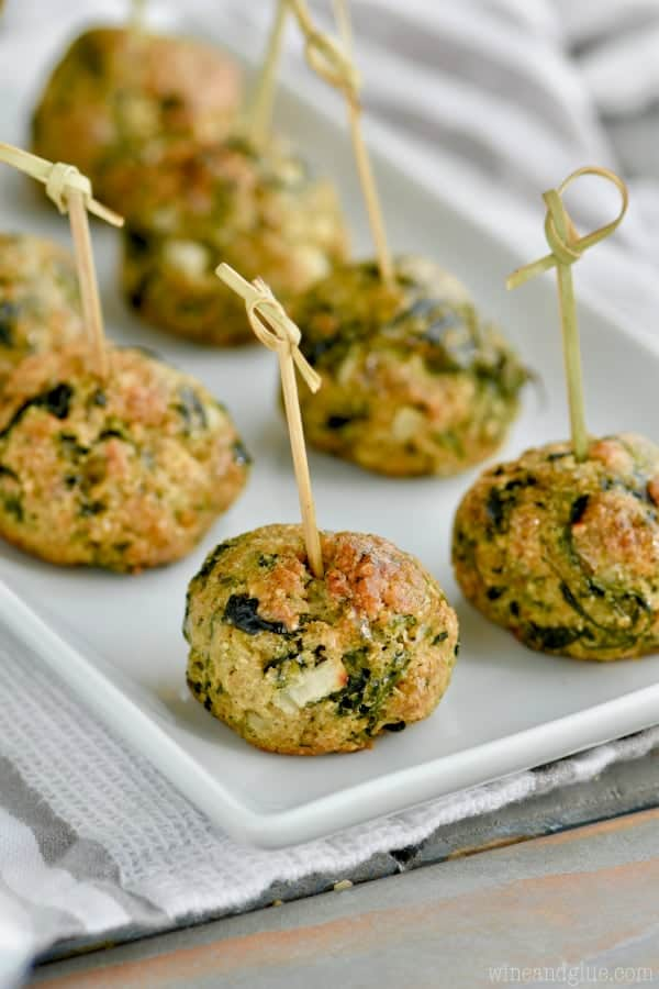 On a white plate and lined up are the Spinach Balls which is a golden brown color.