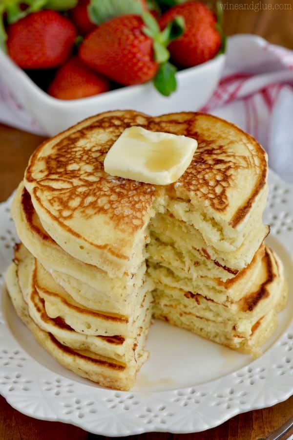 A stack of pancakes with a slice cutout