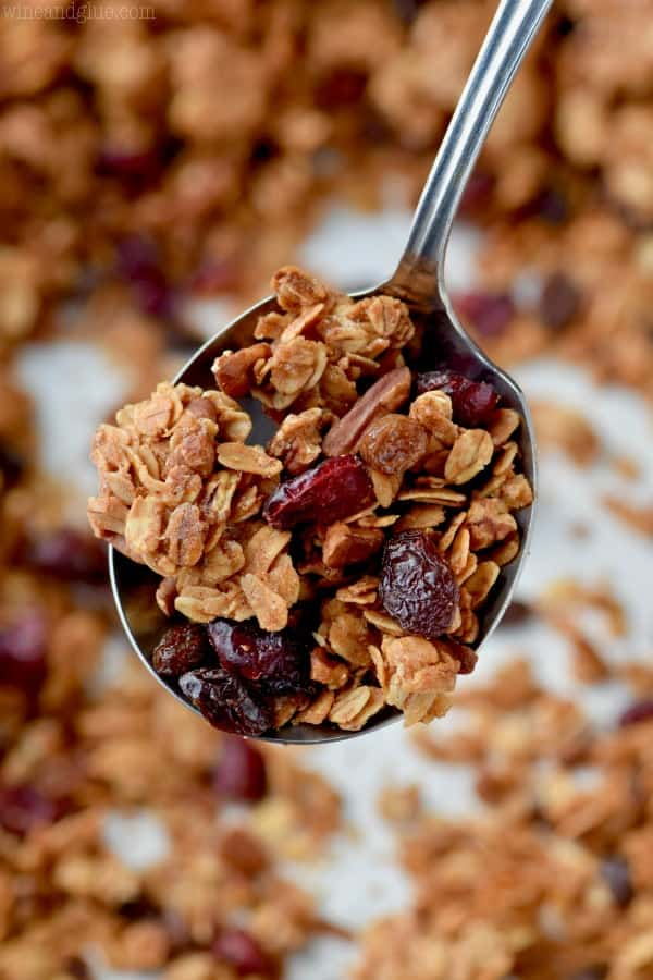 metal spoon holding a spoonful of granola recipe with oats, nuts and dried cranberries visible