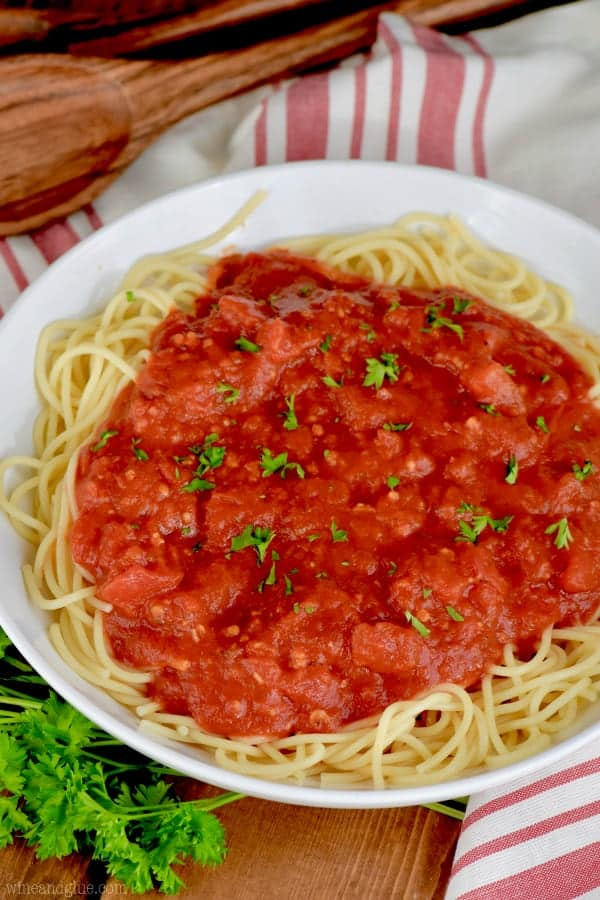 In a white plate is some spaghetti topped with the Easy Homemade Spaghetti sauce and parsley.