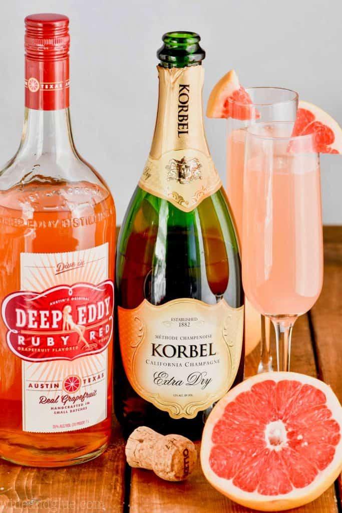 bottle of eddys grapefruit vodka, bottle of champagne and a champagne glass with grapefruit champagne cocktail in it