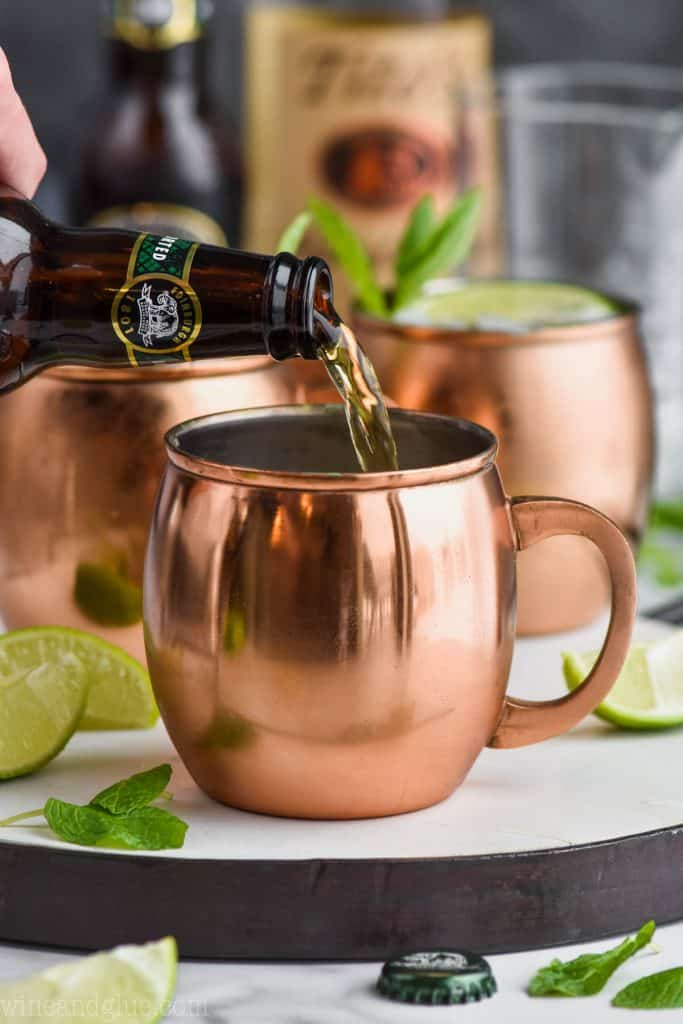 pouring the best ginger beer for a moscow mules into a copper mug
