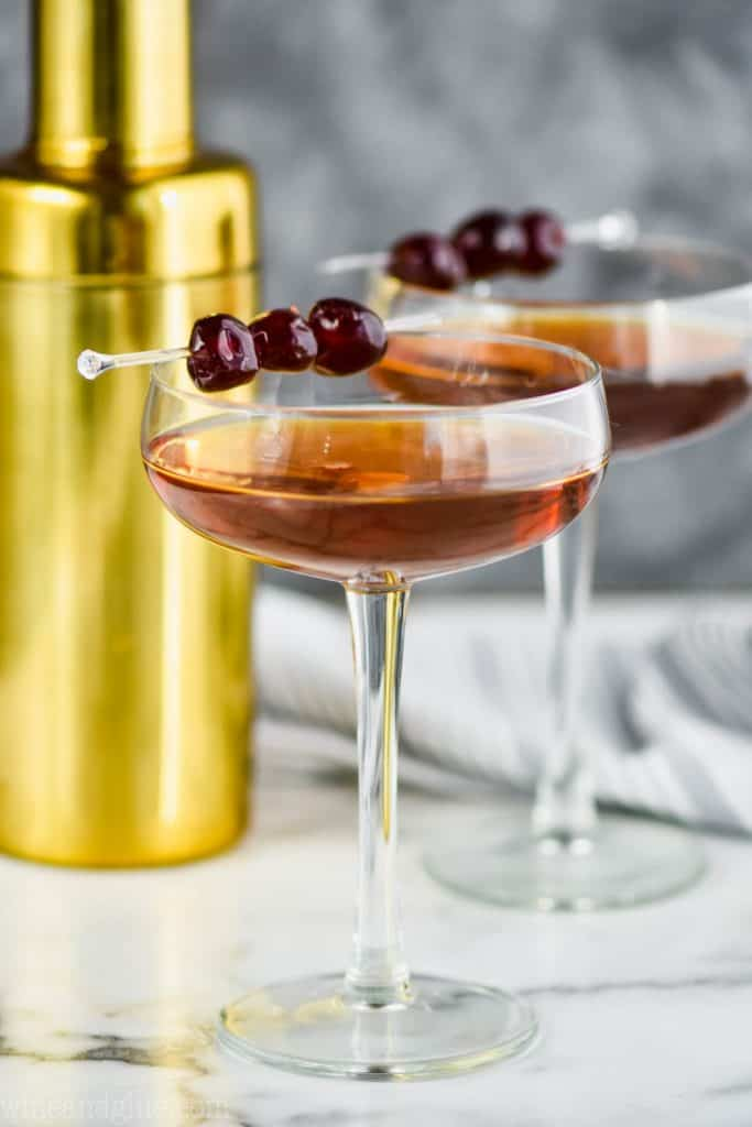 two long champagne coupe glasses filled with a Manhattan drink recipe, garnished with three cherries each, and a gold cocktail shaker in the background