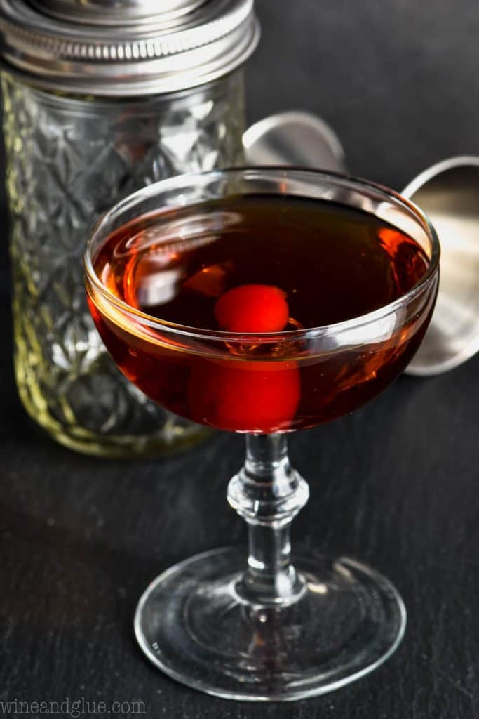 manhattan drink recipe in a small old fashioned cocktail glass with a cherry at the bottom