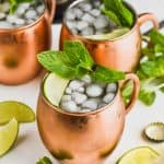 a moscow mule recipe in three copper mugs filled with ice and garnished with mint and lime