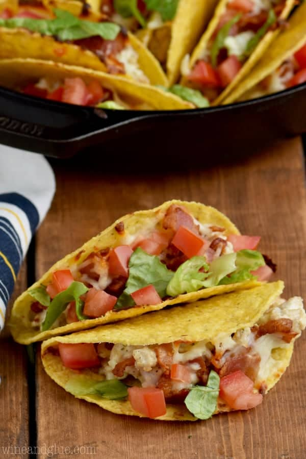 Two Creamy BLT Ranch Oven Baked Tacos are stacked on top of each other with diced tomatoes and lettuce.