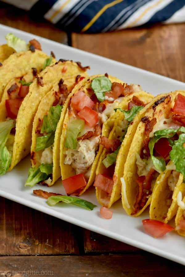 On a white dish, the Creamy BLT Ranch Oven Baked Tacos are next to each other topped with diced tomatoes and lettuce.