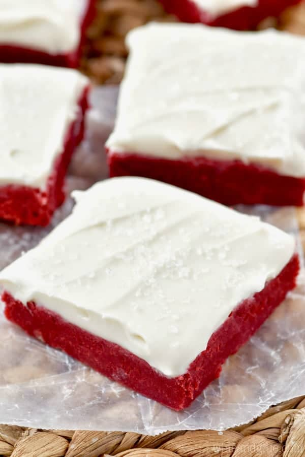 On a piece of parchment paper, the Red Velvet Bars is topped with white frosting and clear sprinkles.