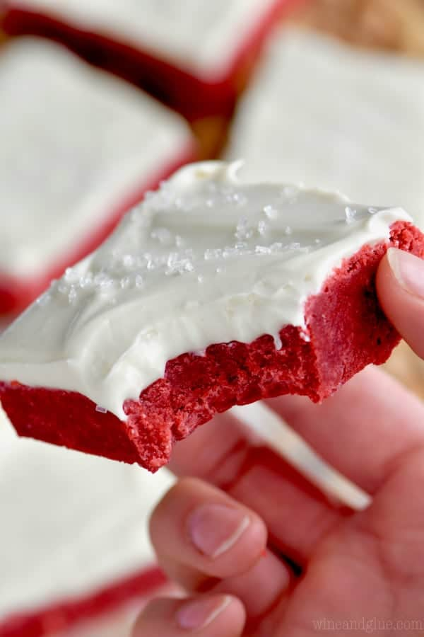 A woman holding a Red Velvet Bars topped with white frosting and clear sprinkles.