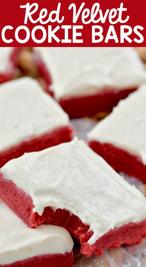 A closeup photo of the Red Velvet Bars with a small bite and topped with white frosting and clear sprinkles.