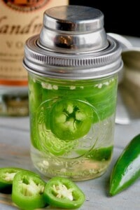 a mason jar full of jalapeno infused vodka
