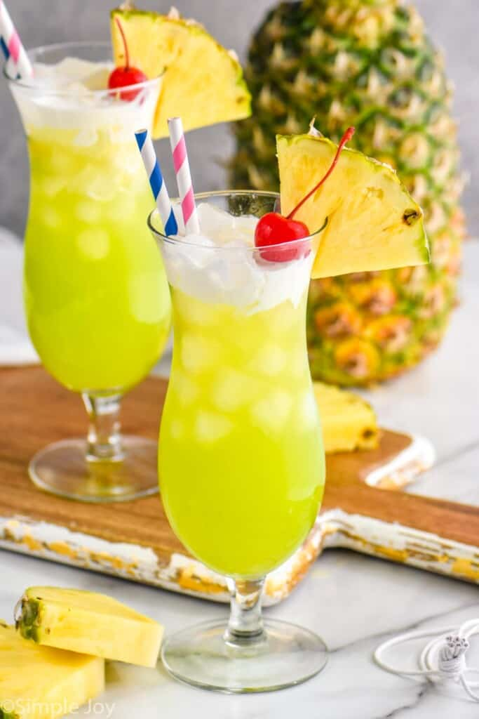 a tall glass filled with midori splice, topped with cream, garnished with a cherry and a pineapple wedge