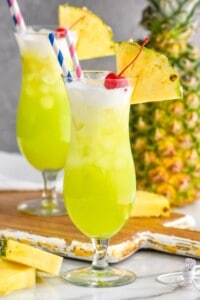 a hurricane glass filled with a midori splice garnished with a cherry and a pineapple wedge, some cream floating on top