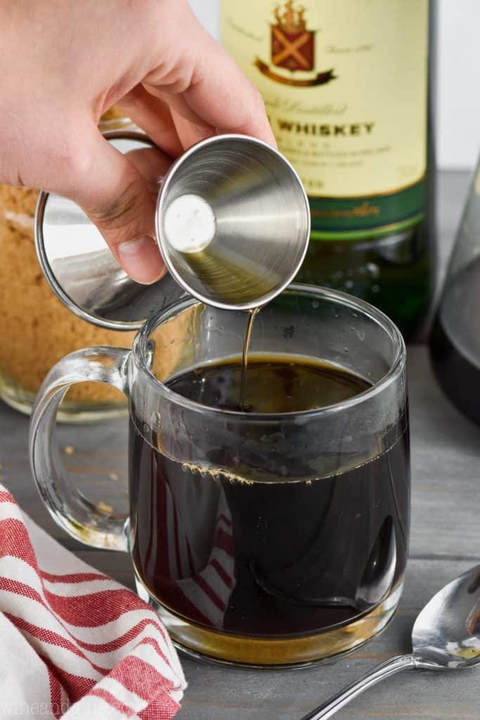 irish whiskey being poured into a cup of coffee to make irish coffee