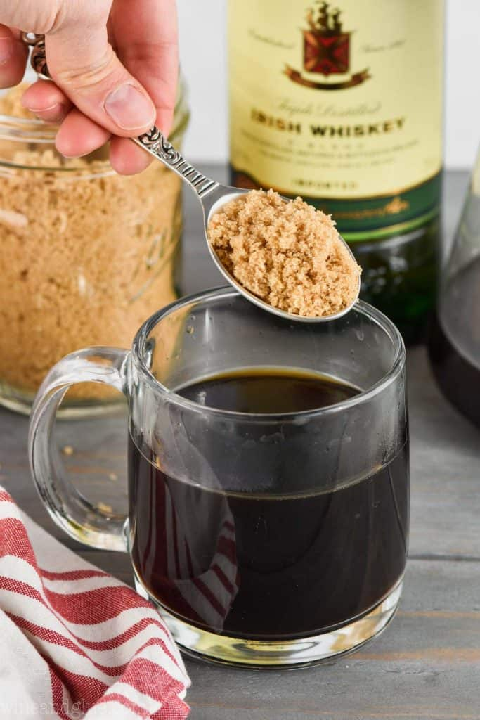 brown sugar being added to coffee for how to make an irish coffee