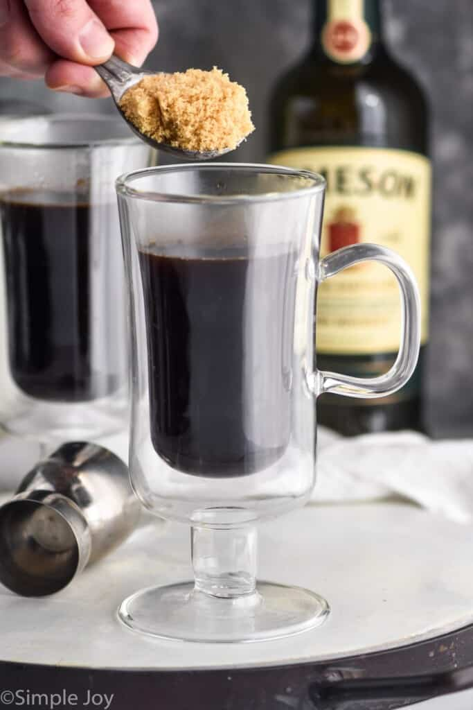 holding brown sugar over a glass of coffee