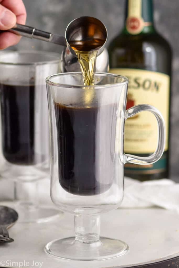 whiskey being poured into a glass of coffee