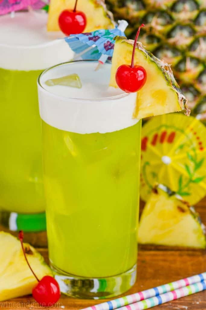a highball glass filled with midori splice and garnished with a cherry and a pineapple slice