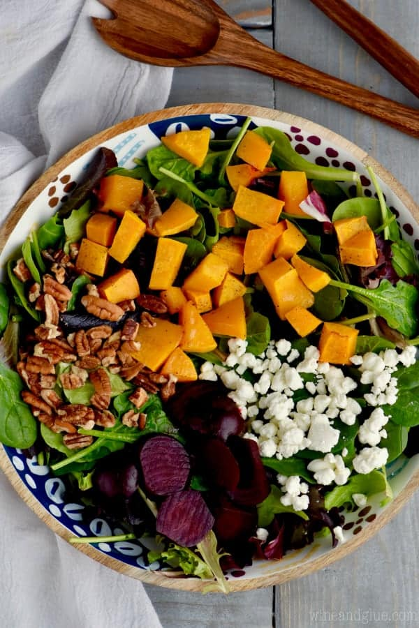 A overhead photo of Roasted Beet Salad with cubbed butternut squash, pecans, goat cheese, mixed greens, and roasted beats.