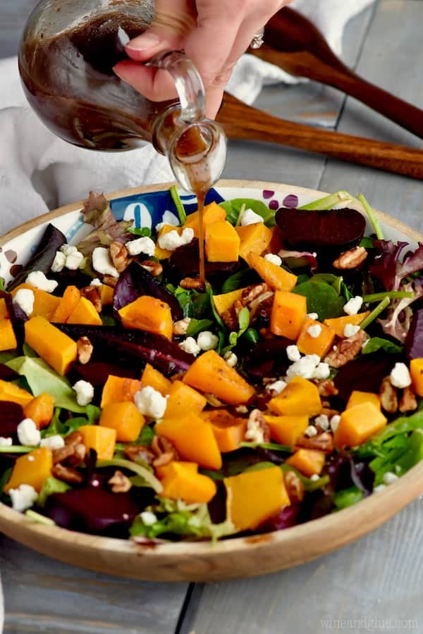 A close up photo of Roasted Beet Salad with cubbed butternut squash, pecans, goat cheese, mixed greens, roasted beats, and balsamic vinegar being poured.