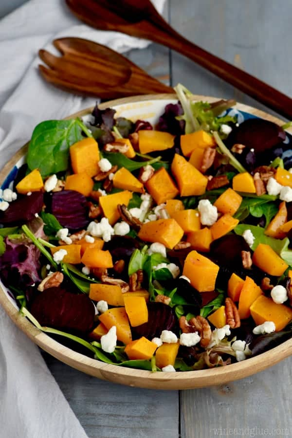 A close up photo of Roasted Beet Salad with cubbed butternut squash, pecans, goat cheese, mixed greens, and roasted beats..