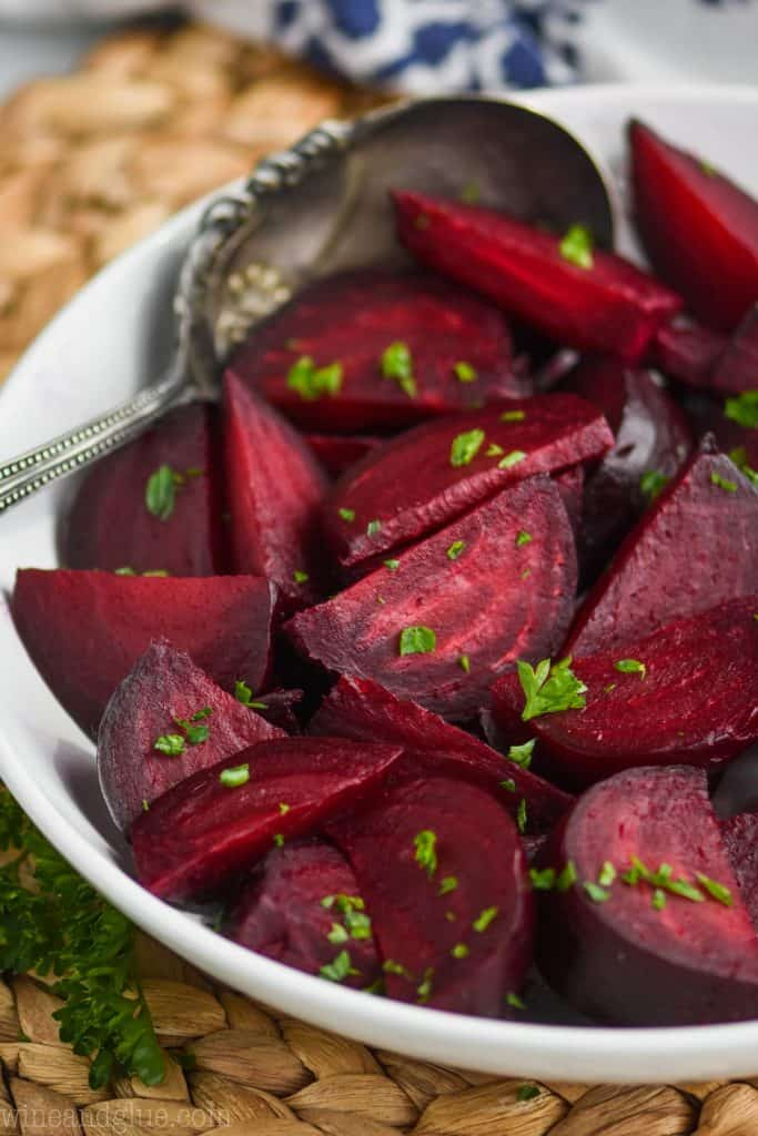 white bowl full of roasted beets recipe and antique spoon, garnished with fresh parsley