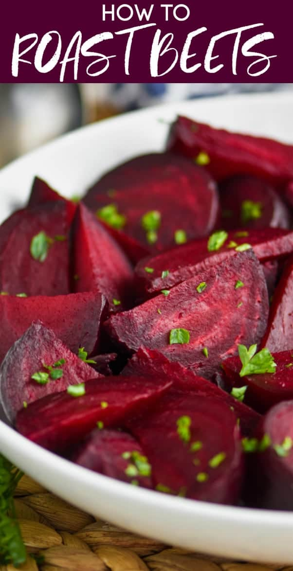 a while bowl on a wood mat filled with wedges of roasted beets sprinkled with parsley