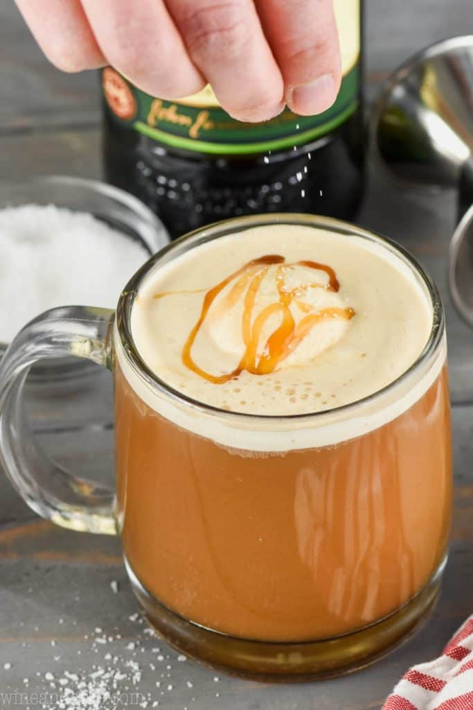 a sprinkle of kosher salt being added to a salted caramel Irish coffee recipe