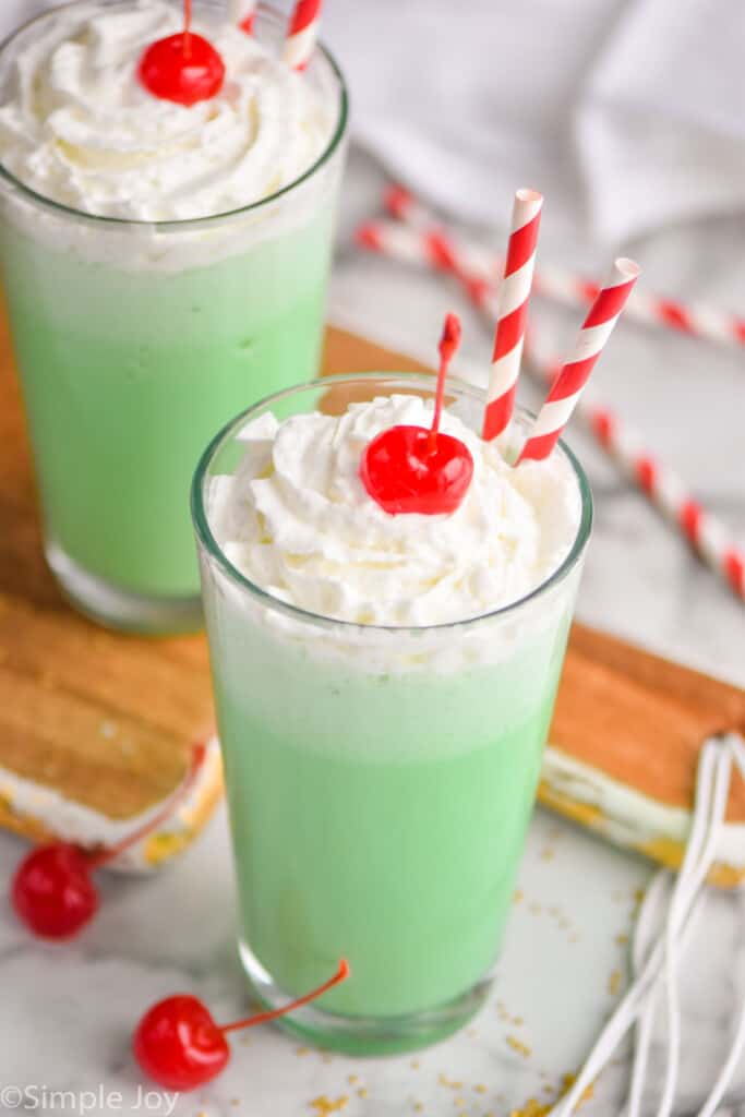 pulled back view of two tumblers filled with shamrock shake, topped with whipped cream and cherries