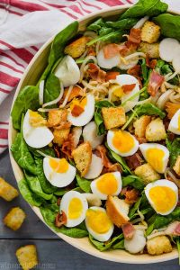 overhead view of spinach bacon salad with hard boiled eggs, croutons, water chestnuts in a white bowl