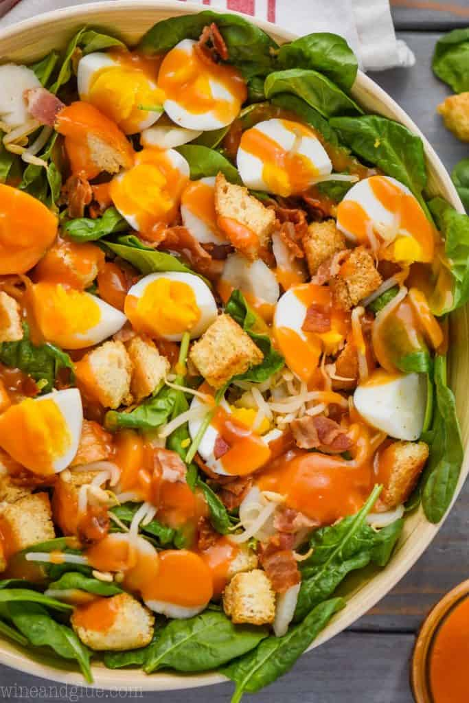 spinach salad with croutons and eggs in a white salad bowl topped with red spinach salad dressing