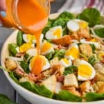woman's handing pouring a mason jar full of red spinach salad dressing onto a spinach bacon salad with hard boiled eggs and croutons in a white bowl